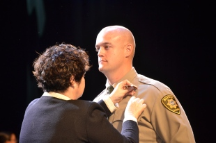 Chief Judge Elizabeth Gonzalez pins official badge to Michael Kyle who graduated under the uniform of the the District Court marshals