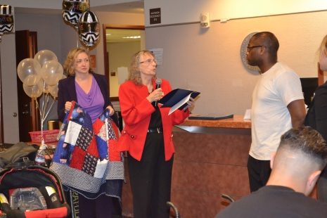Jarenie Trachier presents a veterans' court graduate a Quilt of Valor, specially made by the Quilts of Valor non-profit organization.