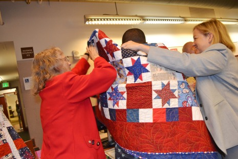 Jarenie Trachier & Judge Linda Bell wrap a veterans' court graduate with a quilt specially made by the Quilts of Valor non-profit organization.