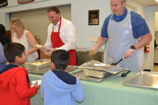 District court Chief Judge Linda Bell, Judge Bill Kephart and volunteer serve up a delicious turkey dinner.